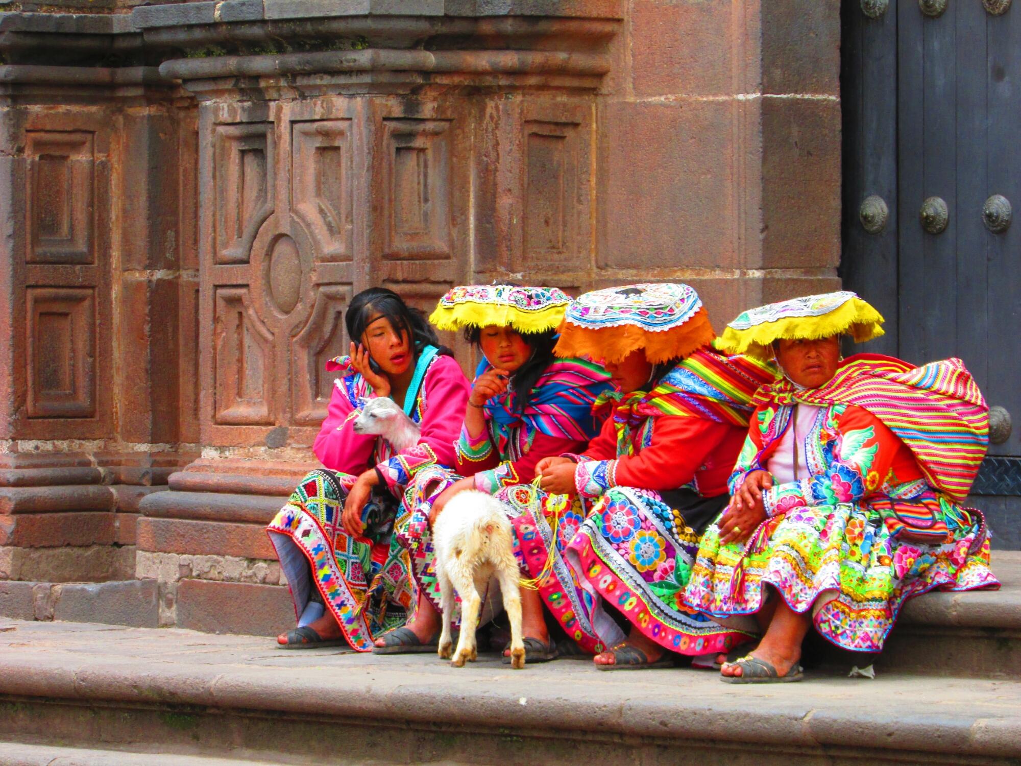 mujeres peruanas en sus vestimentas típicas andinas sentadas a la puerta de una iglesia