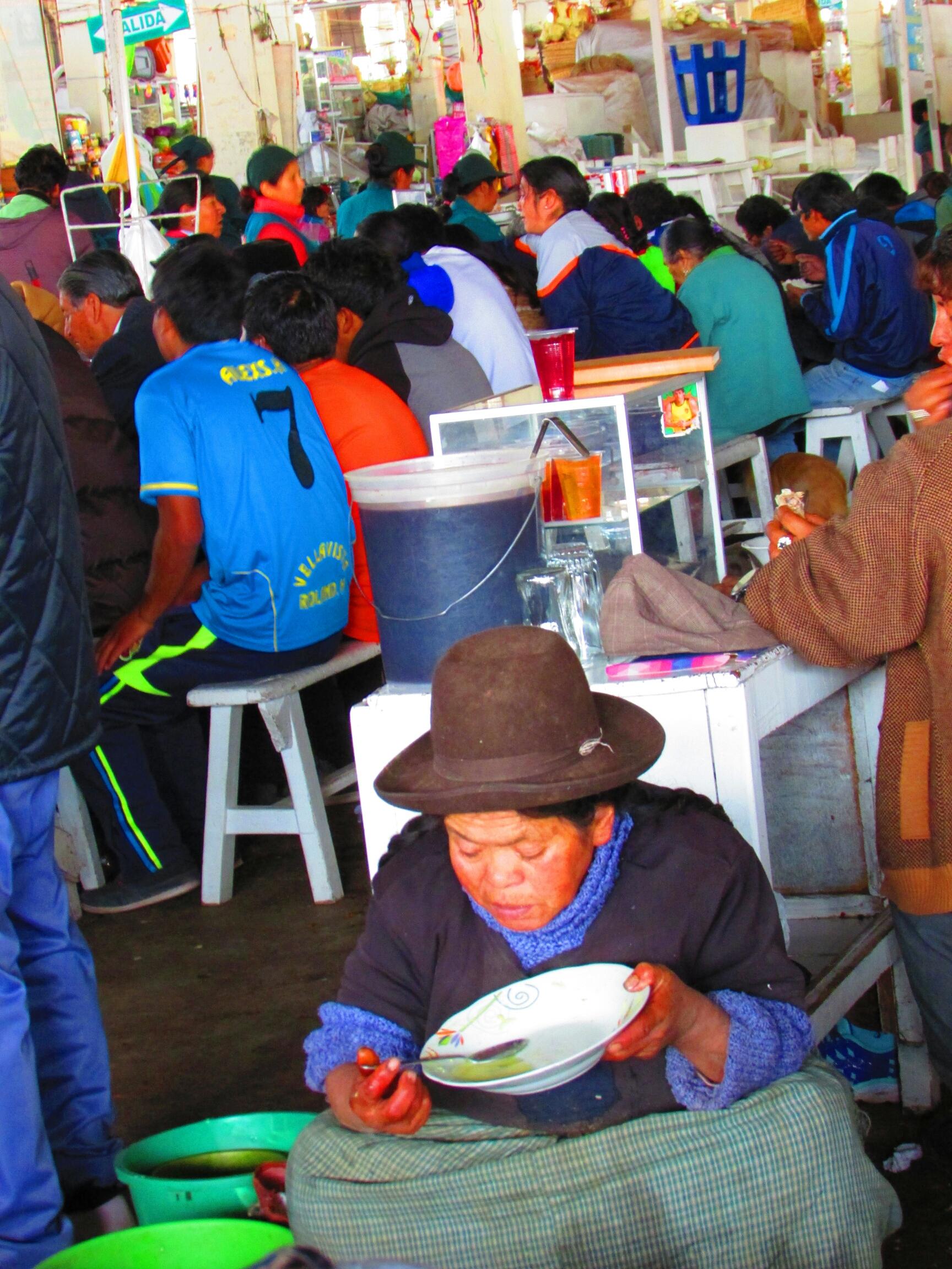 mujer peruana comiendo sentada en el suelo en Mercado de San Pedro en Cuzco