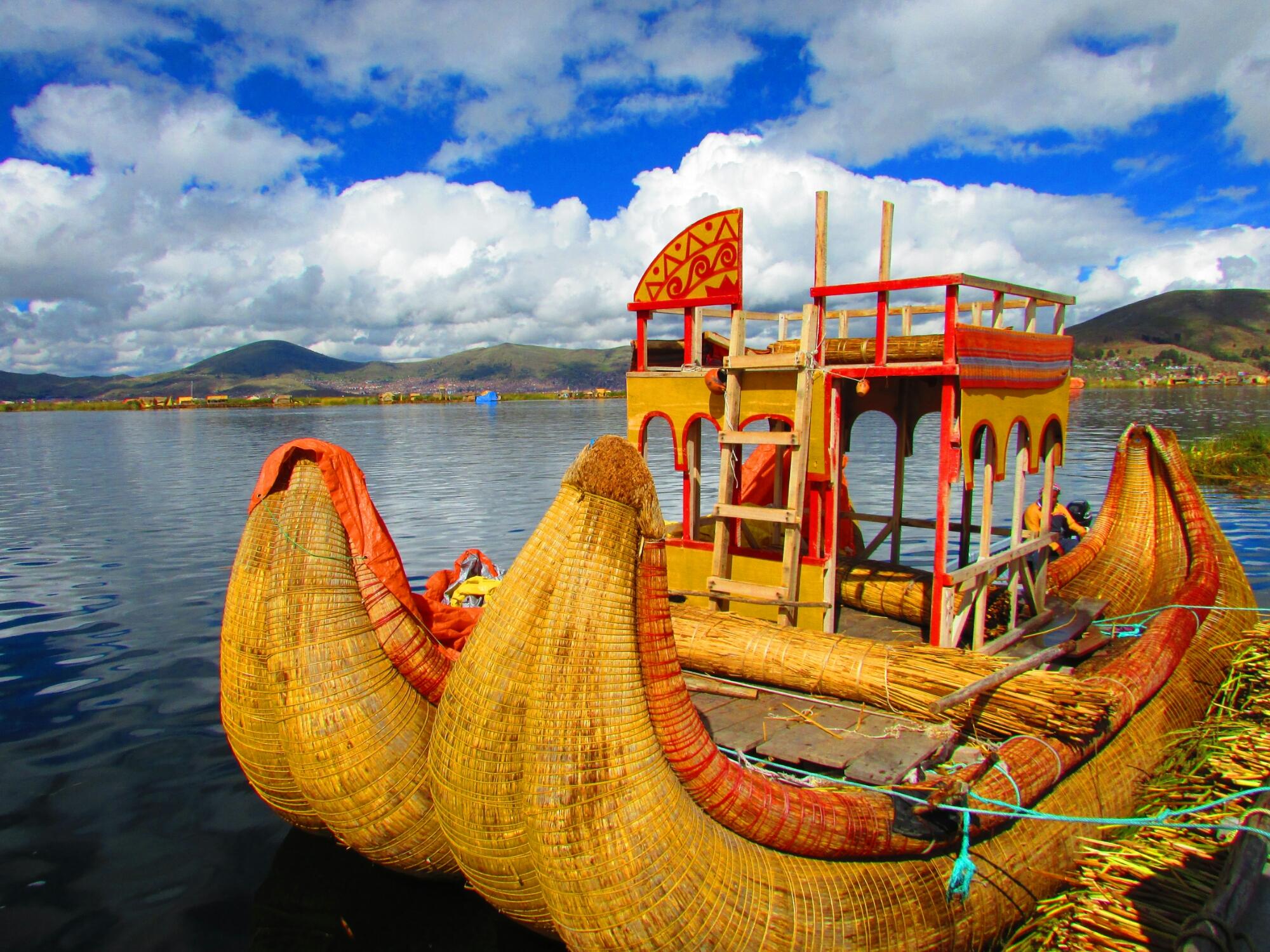 balsas tradicionales y las montañas de fondo en las islas Uros del lago Titicaca